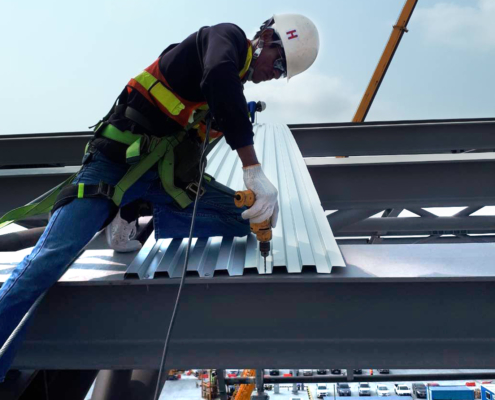 construction worker drilling metal
