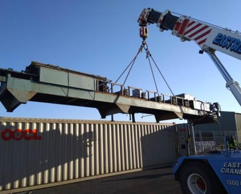 Construction crane lifting a cargo box secured by self cladding studs